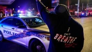 Un homme se tient devant une voiture de police, lors de la manifestation contre la mort de Breonna Taylor par la police de Louisville et de George Floyd par la police de Minneapolis, à Louisville, Kentucky, États-Unis, 2020.