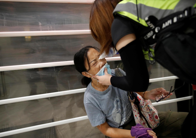Mulher recebe ajuda após ter sido pulverizada com spray de pimenta pela polícia em um shopping center em Tai Po, Hong Kong, em 3 de novembro de 2019