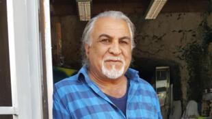 رضا یحیائی در کنار کارگاه شخصی خود که در کنار خانۀ او در دل کوه کنده شده است.