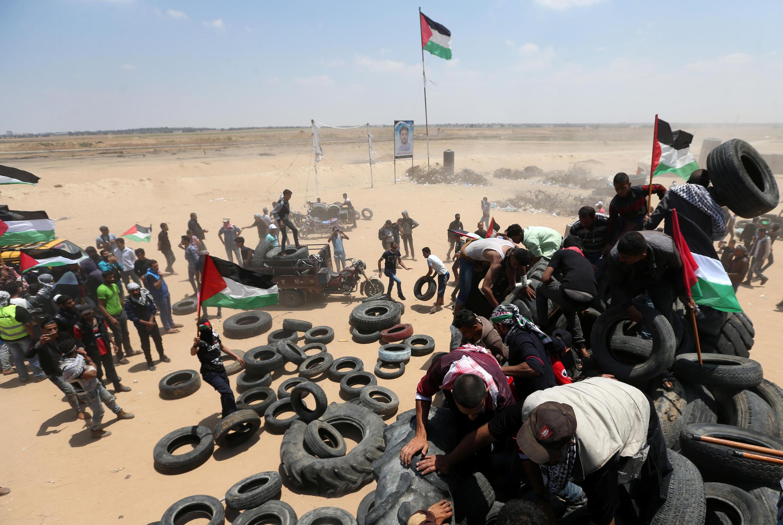 Des palestiniens manipulent des pneus destinés à être brûlés afin de fournir un rideau de fumée protecteur face à l'armée israélienne, le 15 mai 2018 à la frontière entre Gaza et Israël.