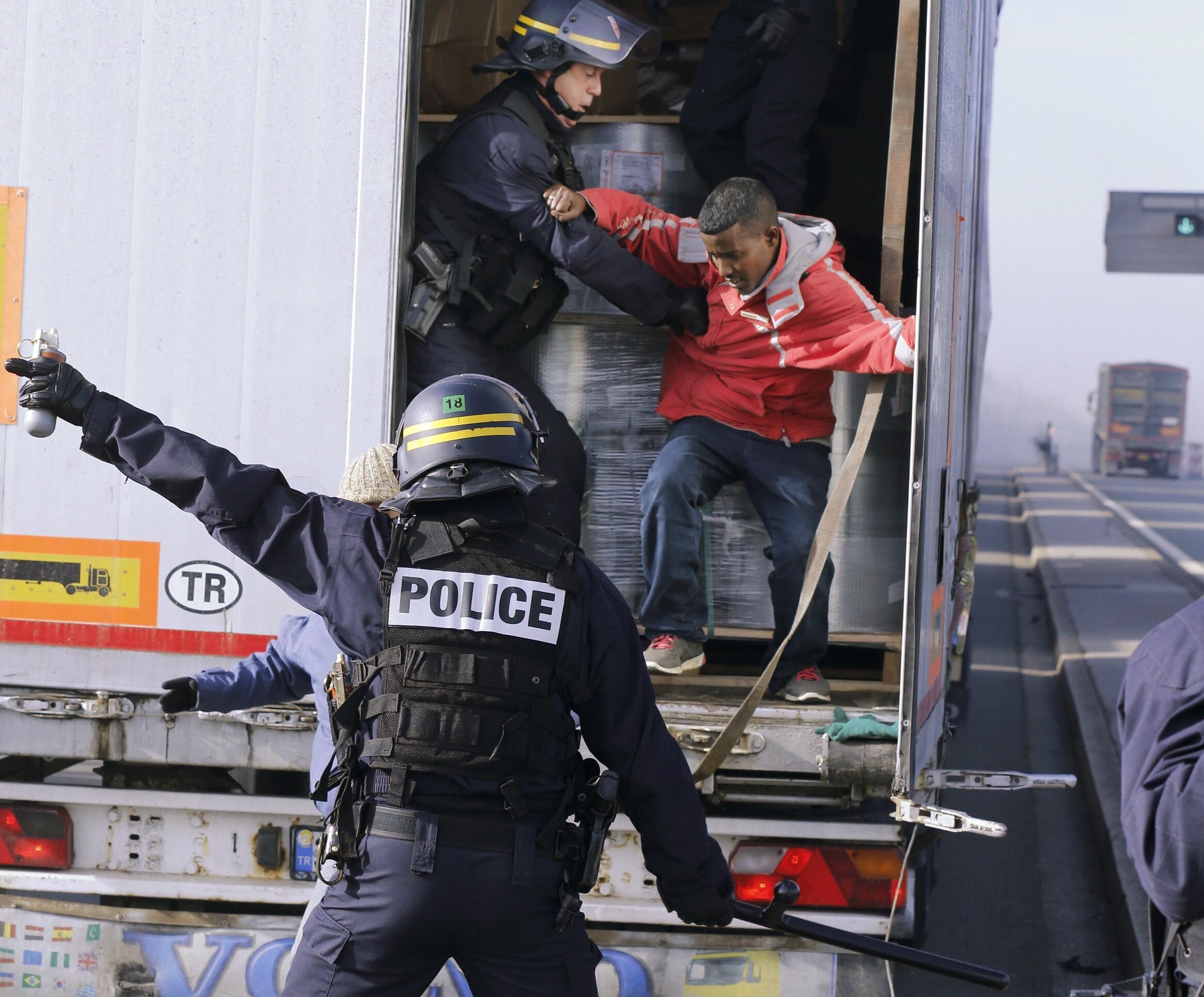 Policiais da tropa de choque retiram imigrantes de um caminhão em Calais