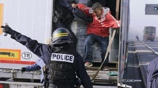 French riot police of the force out immigrants who were hidden in a truck.