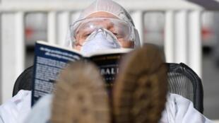 Un homme en combinaison protectrice lit un livre à Dresde, en Allemagne, le 23 mars 2020.
