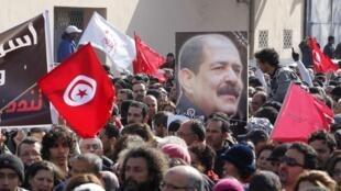 Dans le cortége funèbre, des Tunisiens brandissent le portrait de Chokri Belaid. A Tunis, dans le quartier de Jebel, le 8 février 2013.