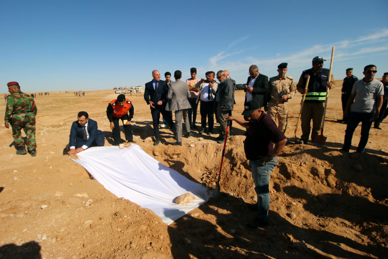 Des membres irakiens de la Défense civile et des responsables recouvrent, dimanche 14 avril, les ossements d'une fosse commune de Kurdes découverte à l'ouest de la ville de Samawa, en Irak.