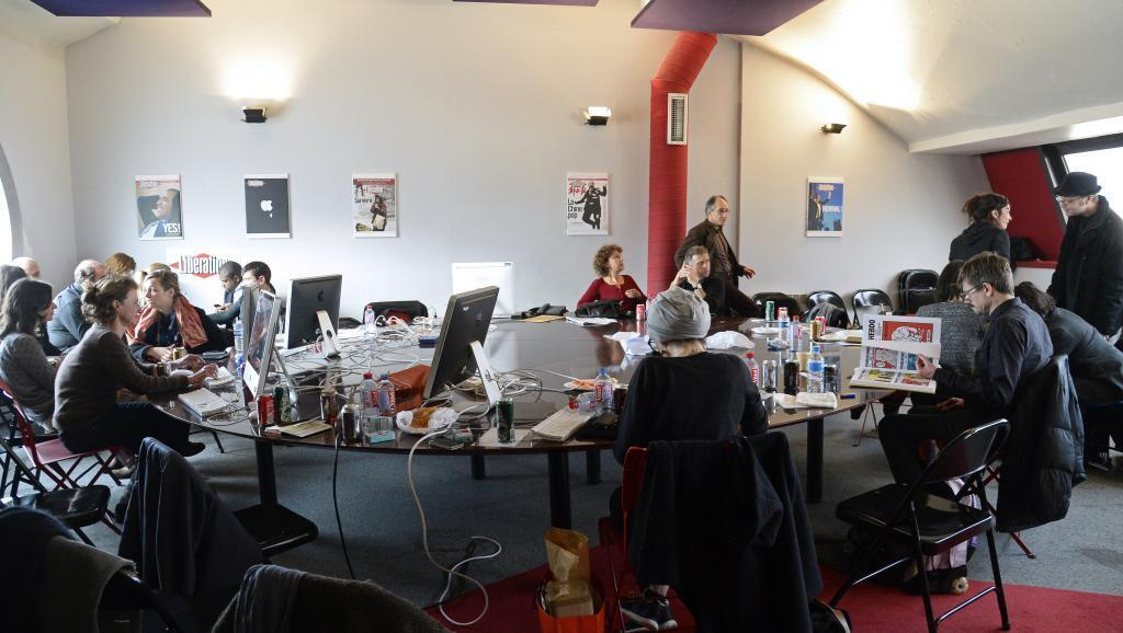 Charlie Hebdo's journalists work on this week's issue in the offices of Libération newspaper in Paris