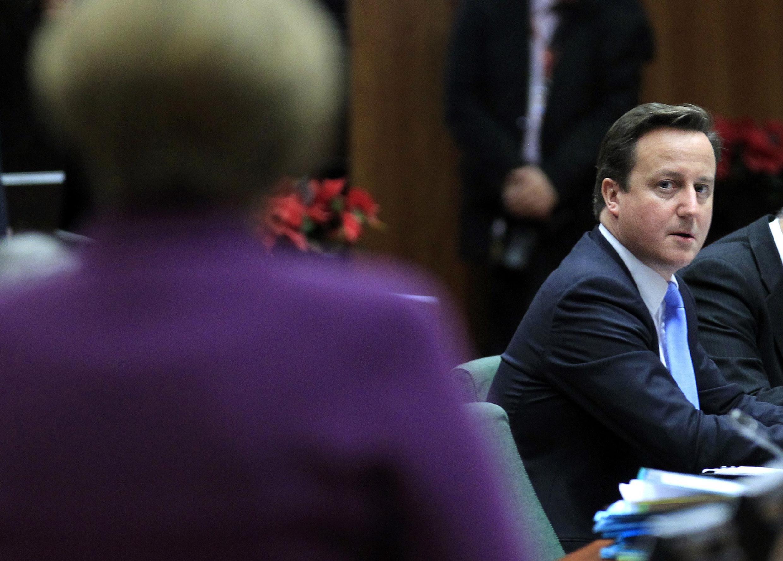 លោក David Cameron សម្លឹងមើលលោកស្រី Angela Merkel ក្នុងជំនួបកំពូលអឺរ៉ុប កាលពីថ្ងៃសុក្រ ៩ ធ្នូ ២០១១