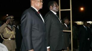 Le président sud-africain Jacob Zuma (g) et son homologue zimbabwéen Robert Mugabe à l'aéroport international d'Harare, le 27 août 2009 (photo d'illustration).