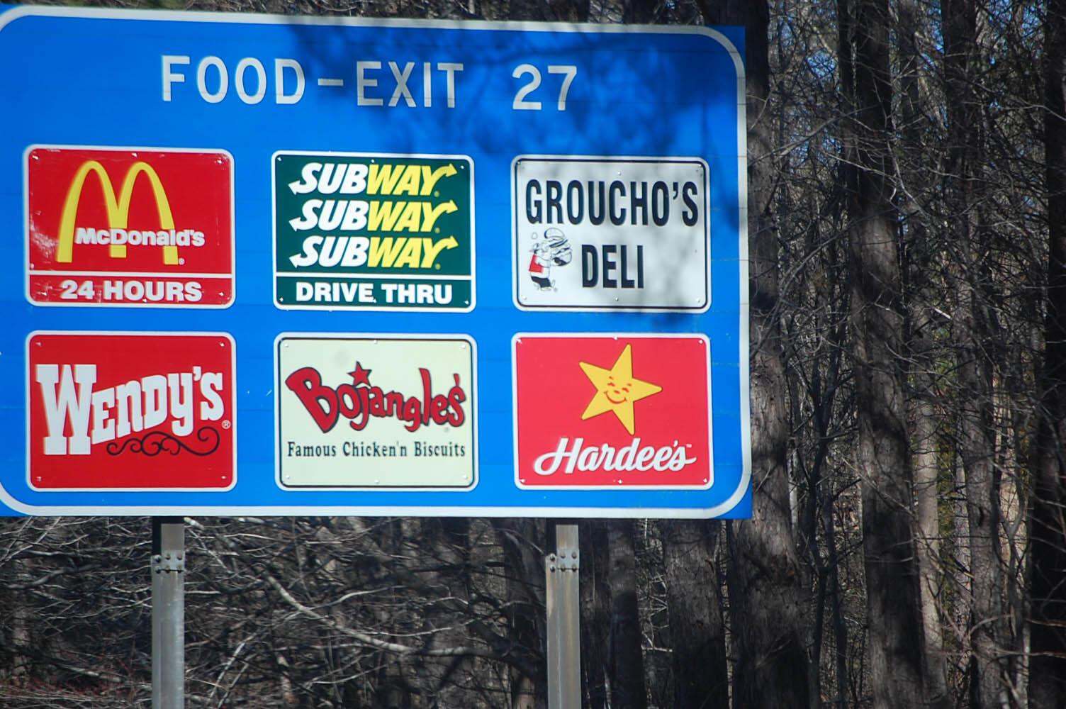 Panneau de signalisation indiquant la présence de plusieurs fast food.