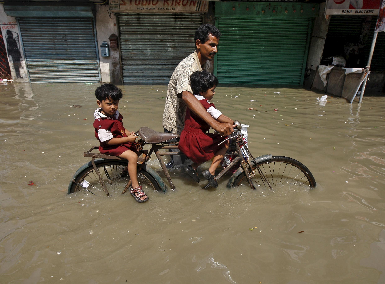 Indiano tenta levar filhas à escola após enchentes que devastaram o leste da Índia em foto de 3 de agosto de 2015.