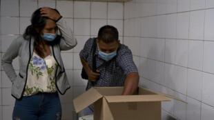 Wendy Dulcey (I) y su esposo observan el cuerpo de su hijo que murió con 39 días en la UCI de un hospital en Caracas
