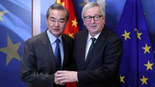 Le ministre chinois des Affaires étrangères, Wang Yi, est accueilli par le président de la Commission européenne, Jean-Claude Juncker, avant une réunion à Bruxelles, en Belgique, le 18 mars 2019.