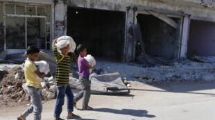 Garotos sírios transportam pão para festejar o fim do Ramadan em Aleppo.
