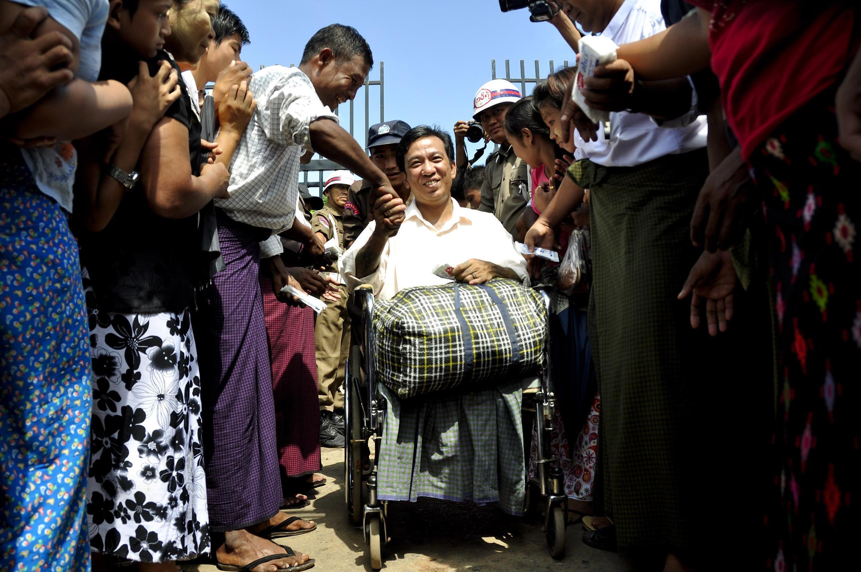 Người dân chào đón một tù nhân đi xe lăn vừa được trả tự do, trước cổng trại giam Insein ở Rangoon ngày 12/10/2011.