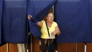 Une électrice roumaine s'acquitte de son devoir civique dans un bureau de vote de Bucarest le 29 juillet 2012.