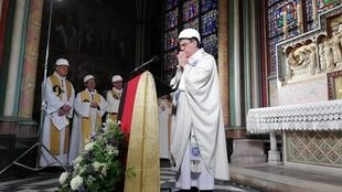 Archbishop of Paris Michel Aupetit, wearing a hard-hat for safety, leading the first mass in Notre-Dame's chapel since the fire, 15 June 2019.