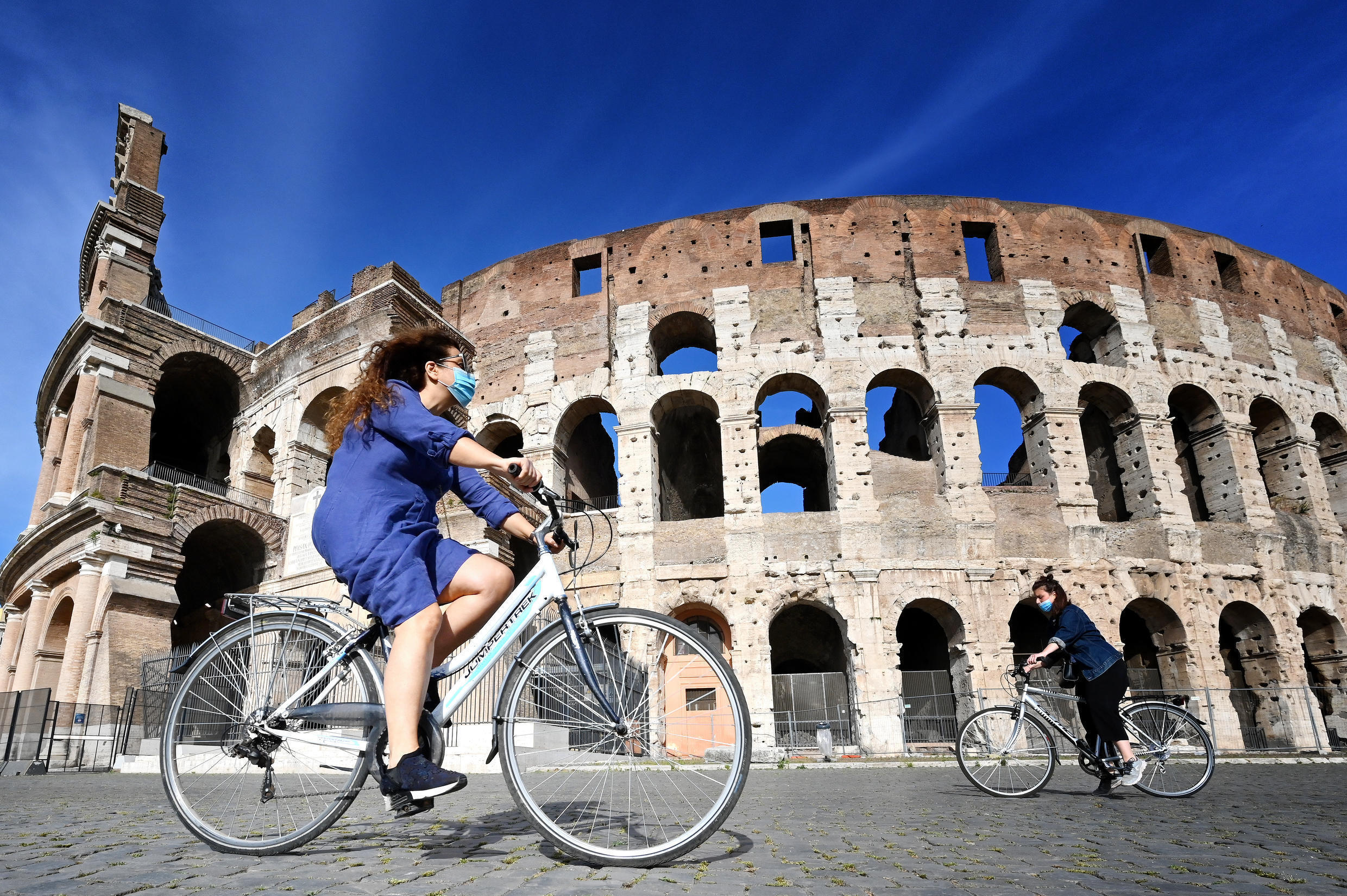 A cyclist rides past Rome's Coliseum, a historical site that will remain closed to the public for the time being, May 2020