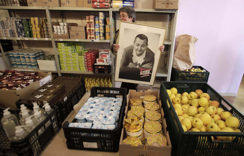 Dans un centre de distribution, une bénévole des Restos du coeur accroche un portrait de Coluche, le fondateur.