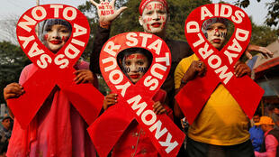 People hold ribbon cut-outs as they pose during an HIV/AIDS awareness campaign on the eve of World AIDS Day in Kolkata.