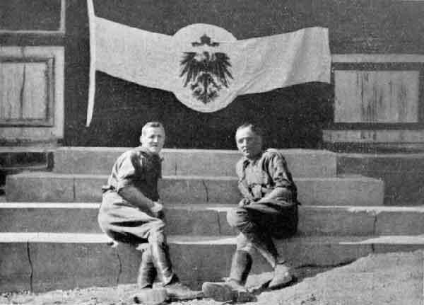 Des officiers sud-africains posent face à un drapeau pris à l'ennemi allemand, à Windhuk en 1915.