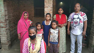 Jyoti Kumari Paswan, wearing a face mask, stands with her family outside their home in the northeastern state of Bihar