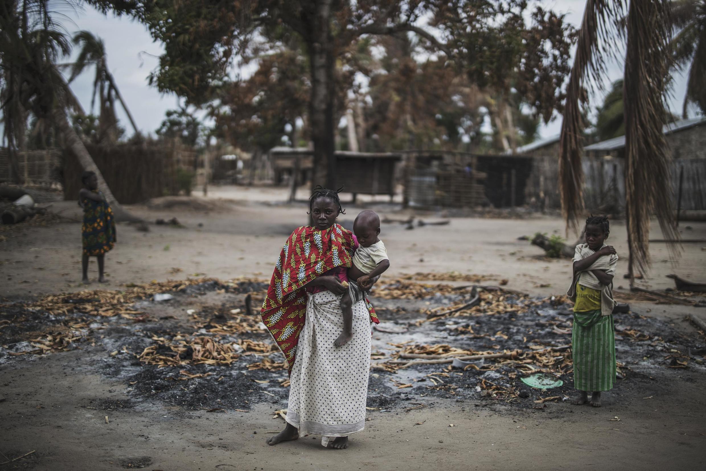Une femme se tient, avec son bébé, sur les ruines de leur village, attaqué en 2019 par des terroristes.