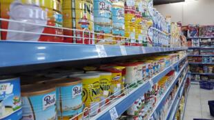 Des boîtes de lait en poudre sur des étagères d'un supermarché en Gambie.