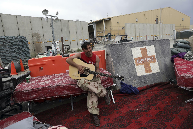 7月5日,一名阿富汗士兵在撤離的美軍留下的Bagram空軍基地門前彈吉他。
