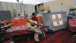 7月5日,一名阿富汗士兵在撤离的美军留下的Bagram空军基地门前弹吉他。