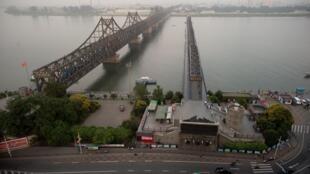 Le soleil se couche sur le pont de l'amitié traversant la rivière Yalu et reliant la ville nord-coréenne de Sinuiju à la ville chinoise frontalière de Dandong le 5 juillet 2017.