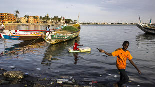Boys playing by the river in Sain-Louis, Senegal
