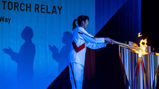 Une porteuse de la torche olympique, l'ancienne volleyeuse Motoko Obayashi, lors du deuxième jour du relais de la flamme, le 26 mars 2021 à Aizuwakamatsu, dans le centre du Japon
