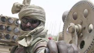 Au Soudan, un militaire gouvernemental pose sur un blindé de fabrication chinoise.