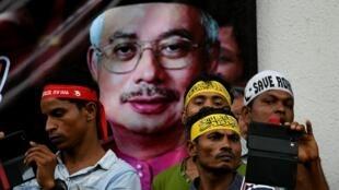 Người Rohingya tị nạn tại Malaysia, trên nền hình ảnh thủ tướng Najib Razak, biểu tình tại Kuala Lumpur, ngày 04/12/2016.