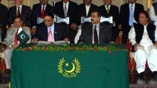 Le président Zardari (2e à gauche) signe l'amendement constitutionnel sous le regard de son Premier ministre Asif Ali Gilani à Islamabad, le 19 avril 2010.