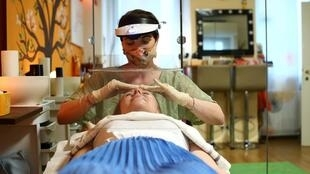 Une esthéticienne, Martina Sekkal, effectue un traitement du visage pour un client lors de l'épidémie de coronavirus  à Vienne, en Autriche, le 2 mai 2020.