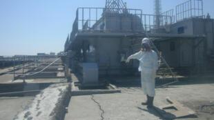 Un employé de la centrale de Fukushima montre une fissure dans le béton à proximité du réacteur n°2, le 2 avril 2011.