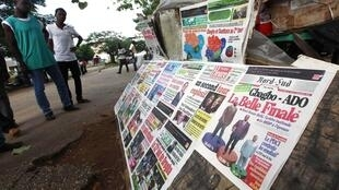 Abidjan, en face d'un kiosque à journaux, des ivoiriens lisent les résultats provisoires du premier tour des présidentielles, le 04 novembre 2010.