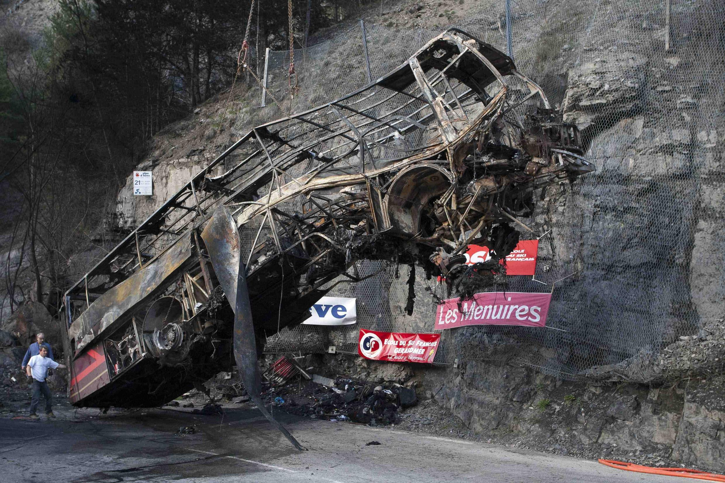 A crane hoists the frame of the bus which crashed and burned on the road from l'Alpe d'Huez