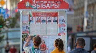 Des habitants de Minsk devant une affiche de la campagne présidentielle. Le 7 aout 2020.