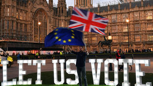 An anti-Brexit protester waves flags outside the Houses of Parliament in London, Britain, March 27, 2019.