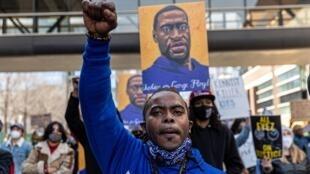 Manifestantes sostienen carteles en honor a George Floyd fuera del Tribunal del Condado de Hennepin en Minneapolis, Minnesota