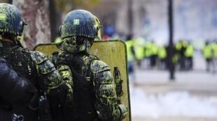 Des CRS aspergés de peinture jaune, ce samedi 1er décembre sur les Champs-Elysées, à Paris, en marge du mouvement des «gilets jaunes».