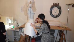 Una asistente trabaja un modelo de la próxima colección de Frank Sorbier,sobre un maniquí.