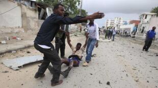 Des civils évacuent un blessé après l'attaque qui a visé des locaux des Nations unies à Mogadiscio.