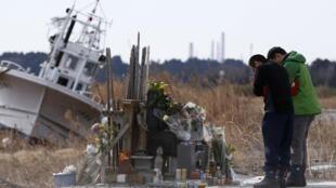 Des Japonais en pleine prière sur les lieux du tsunami, dans la province de Fukushima, le 11 mars 2014.