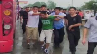 警方带走劫持客车的歹徒之一,图片取自一录像。2011年8月30日。