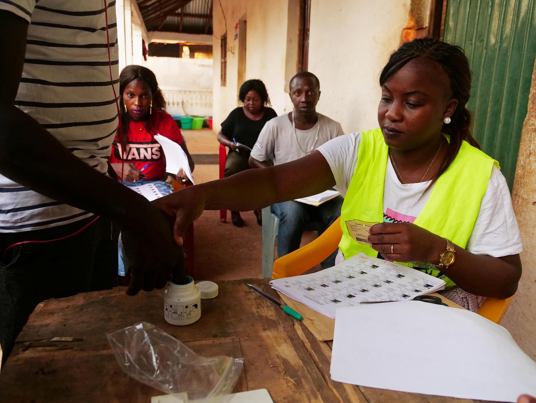 Daya daga cikin jami'an zabe a Guinea-Bissau yayin tantance masu kada kuri'a.