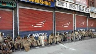 Indian police rest in front of closed shops after Tuesday's clashes with protesters