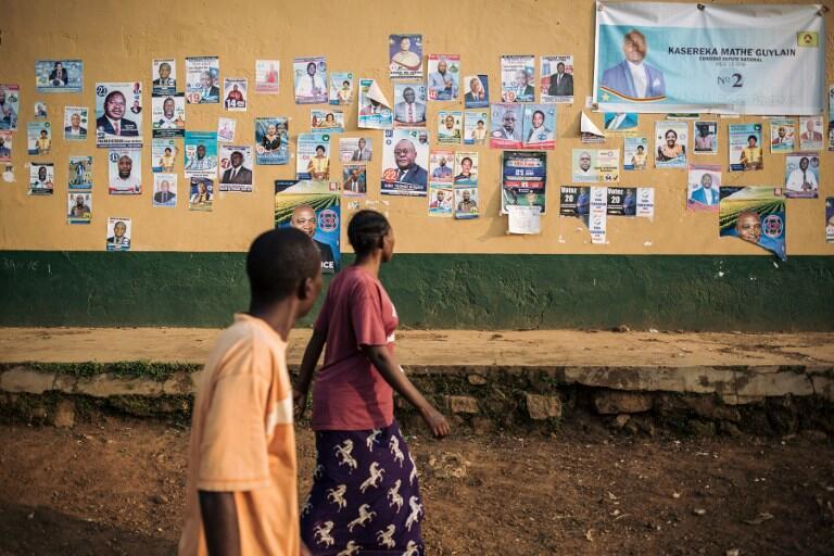 Des habitants de Beni passent devant les affiches des candidats aux élections (image d'illustration).